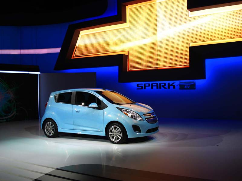 Spark EV side view, with large chevy symbol on wall above